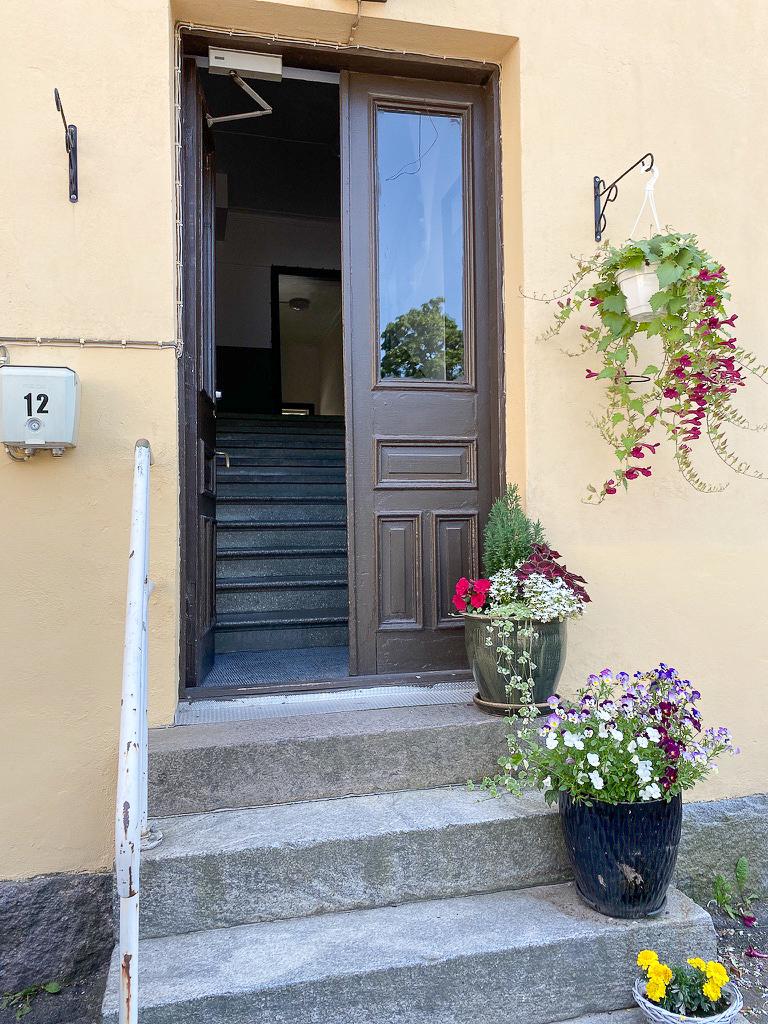 Sisäänkäynti ja kukkaistutuksia.